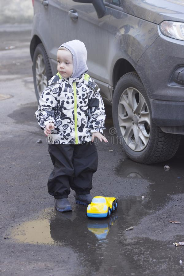 En 2-årig pojke som spelar med en leksakbil i en pöl nära en verklig bil royaltyfri bild