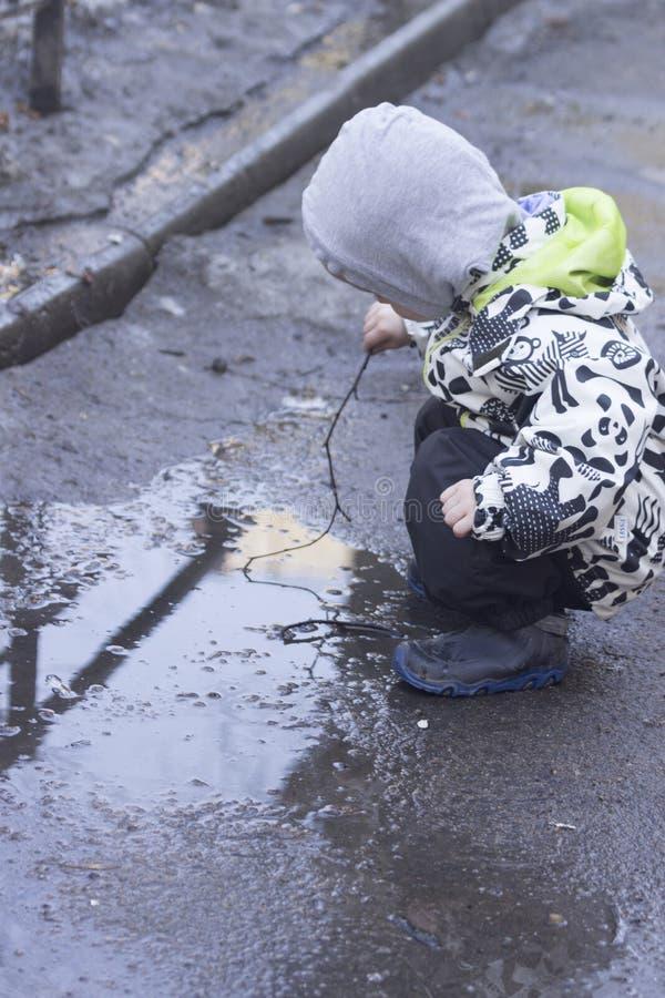 En 2-årig pojke som spelar med en träpinne i en pöl arkivfoton