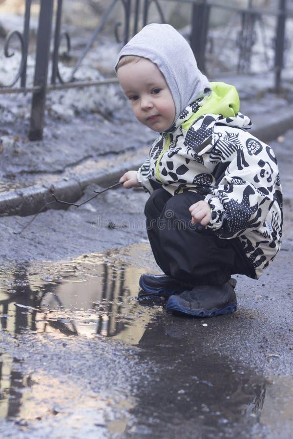 En 2-årig pojke som spelar med en träpinne i en pöl royaltyfri foto