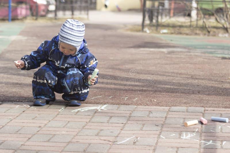 En 2-årig pojkemålning med krita utomhus arkivbilder