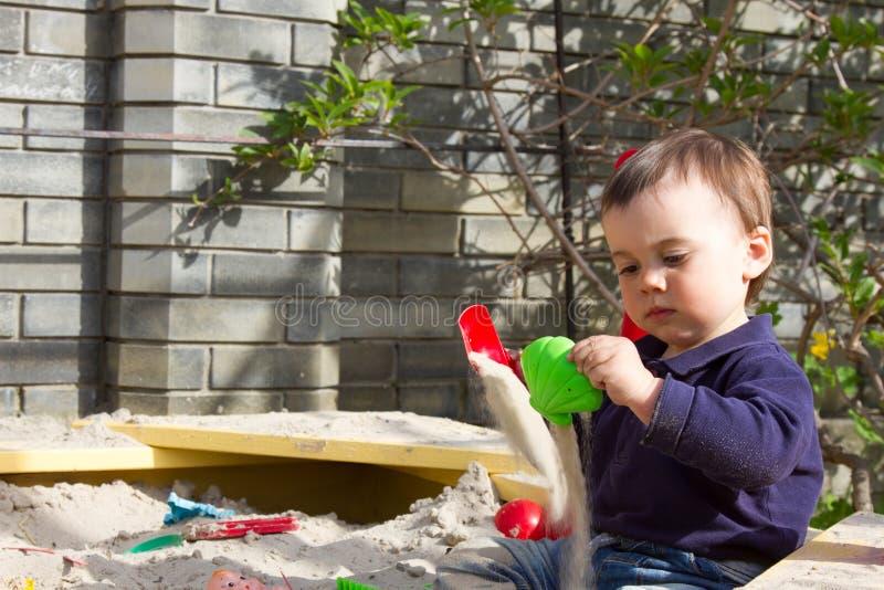 En årig pojketagandeform av sand i sandlådan i trädgården på en solig vårdag fotografering för bildbyråer