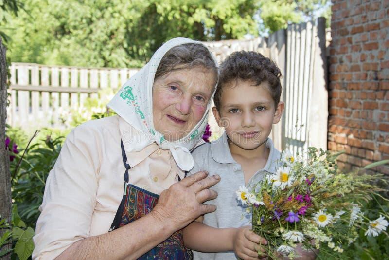 En été, la grand-mère de jardin avec son petit-fils, il est holdi photos libres de droits