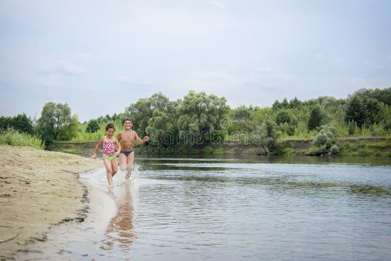 En été, les enfants courent le long de la berge image libre de droits