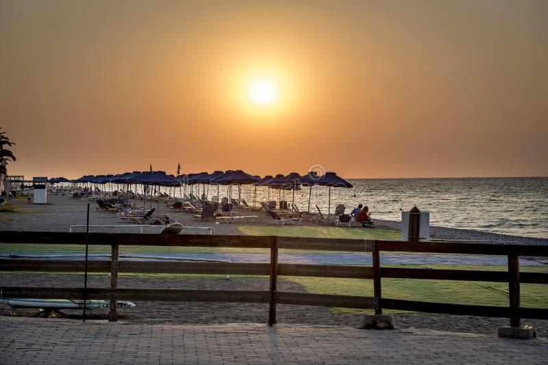 En öde strand med solparaplyer på solnedgången arkivbild