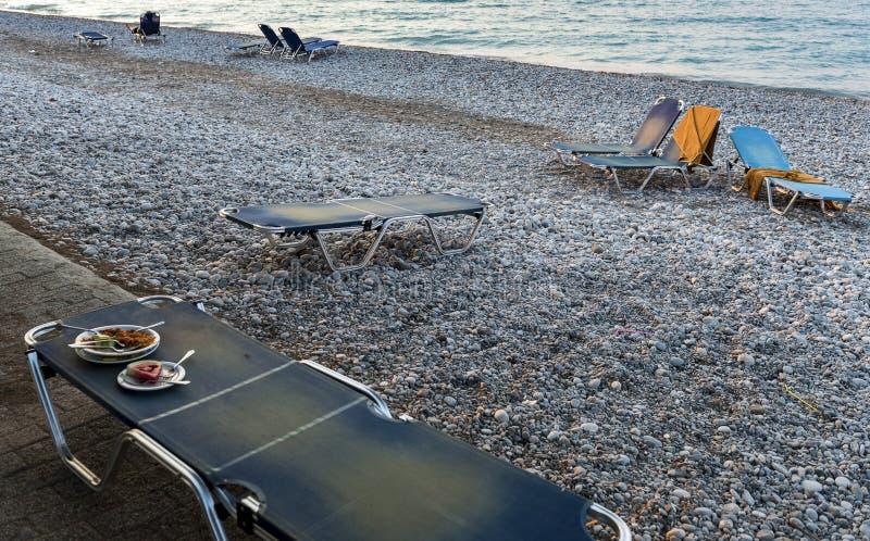 En öde strand och en solstol med kvarlevor av matställen arkivbild