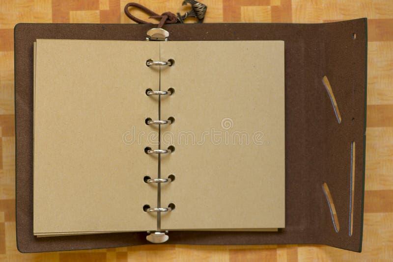 En öppen anteckningsbok med vita sidor som gör anmärkningar arkivbilder