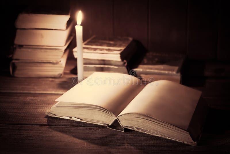 En öppen bok med tomma sidor ligger på en trätabell arkivbilder