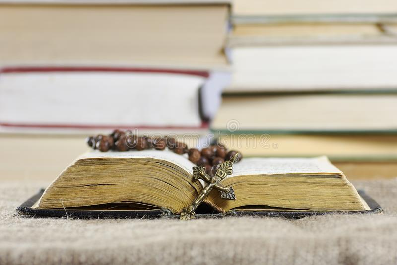 En öppen gammal bok med en radband med suddiga böcker i backgroen arkivfoton