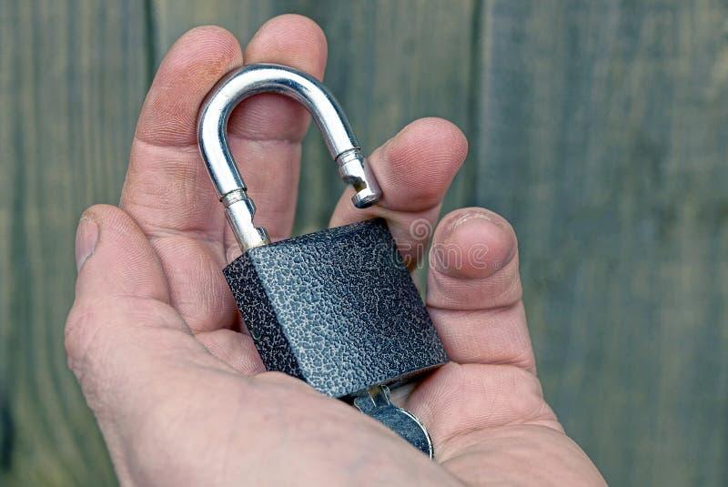 En öppen grå hänglås med en tangent på det öppet gömma i handflatan arkivfoto