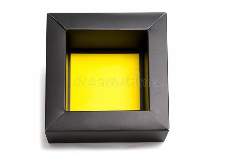 En öppen liten svart kartong med en gul botten Isolerad modell på vit bakgrund royaltyfri foto