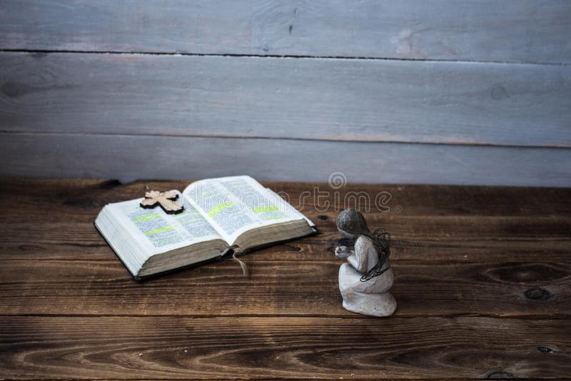 En öppet bibel och kors för ängel royaltyfri foto