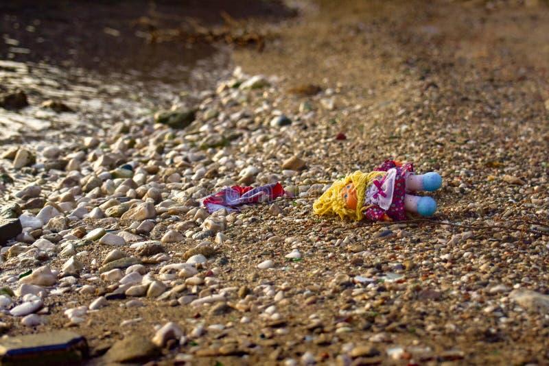 En övergiven docka som lämnas på stranden arkivfoton