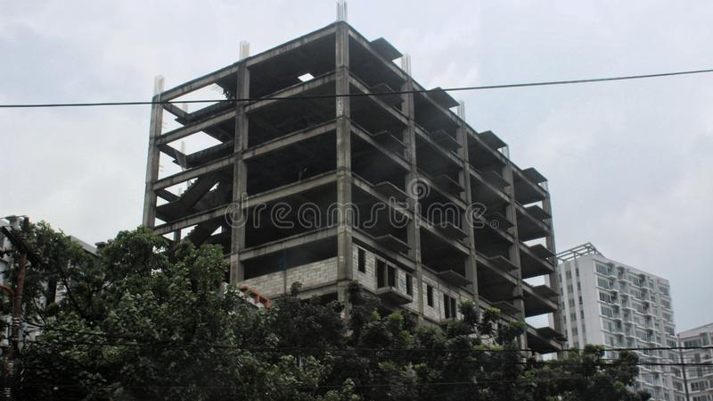 En övergiven gammal byggnad nära en ny lägenhetskomplex royaltyfri bild