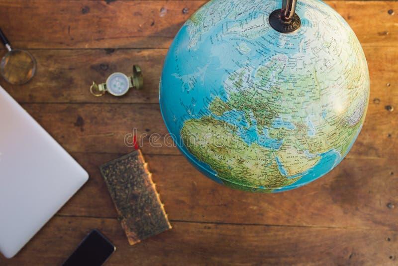 En översikt av världen med en anteckningsbok, en kompass, en smart telefon royaltyfria bilder