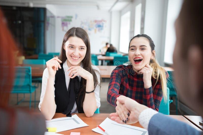 En affärskonferens Två unga kvinnor som sitter vid tabellen och gör en handskakning arkivbild