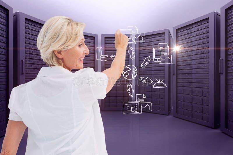 En affärskvinna drar diagrammet mot serverrumbakgrund arkivfoto