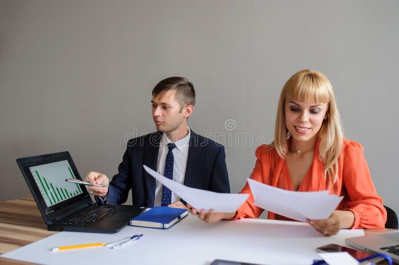 En affärskvinna och man på ett kontorsskrivbord som arbetar på projecen arkivbilder