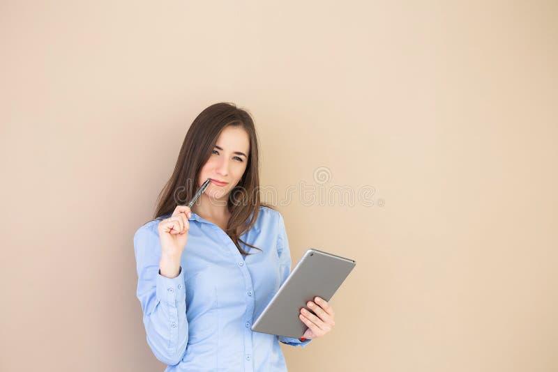 En affärskvinna som använder minnestavlan som isoleras på beige bakgrund royaltyfri bild