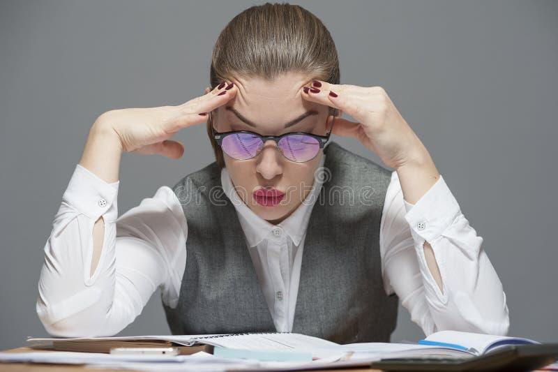 En affärskvinna som känner sig utmattad och trött arkivfoto