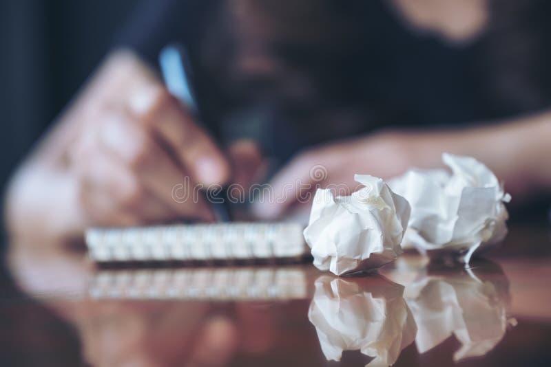En affärskvinna som ner arbetar och skriver på en vit tom anteckningsbok med skruvad upp legitimationshandlingar på tabellen royaltyfria bilder