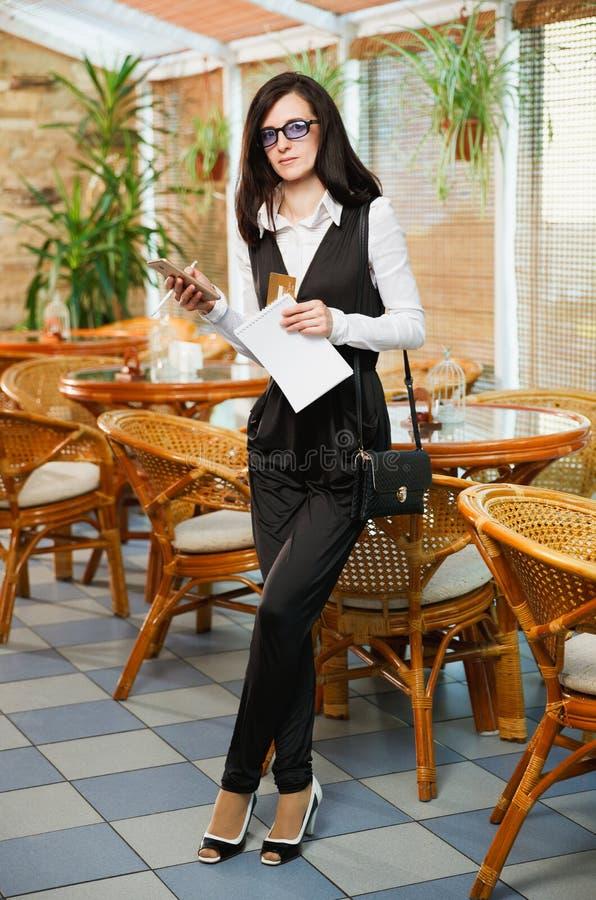 En affärskvinna står i ett kafé med en mobiltelefon och ett a royaltyfria bilder