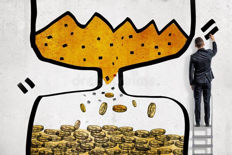 En affärsman avslutar sig att dra ett timglas med sand som ner faller och vänder in i guld- mynt royaltyfri fotografi