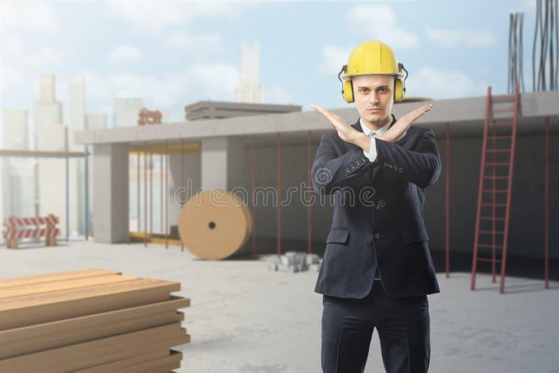 En affärsman bär en gul hjälm på en konstruktionsplats och gör en stopprörelse med hans korsade armar royaltyfri bild