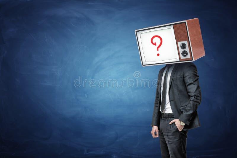 En affärsman har en hand i ett fack och ett huvud som byts ut av en olje- TV med en frågefläck på skärmen royaltyfria foton