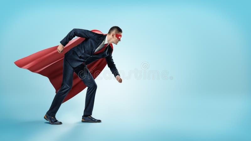 En affärsman i en röd udde för superhero och ett maskeringsanseende i den startande linjen position på blå bakgrund arkivbilder