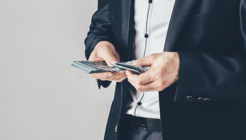 En affärsman i en lyxig svart dräkt rymmer dollar i hans händer Mannen räknar hans pengar arkivfoton
