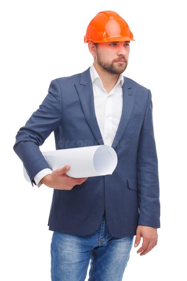 En affärsman med hjälmen på hans huvud, blickar in i avståndet och håll som en hoprullad whatman skyler över brister fotografering för bildbyråer