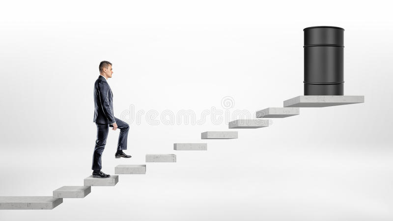 En affärsman på vit bakgrund som går upp trappa för ett konkret kvarter var en svart olje- trumma står på överkanten royaltyfria bilder