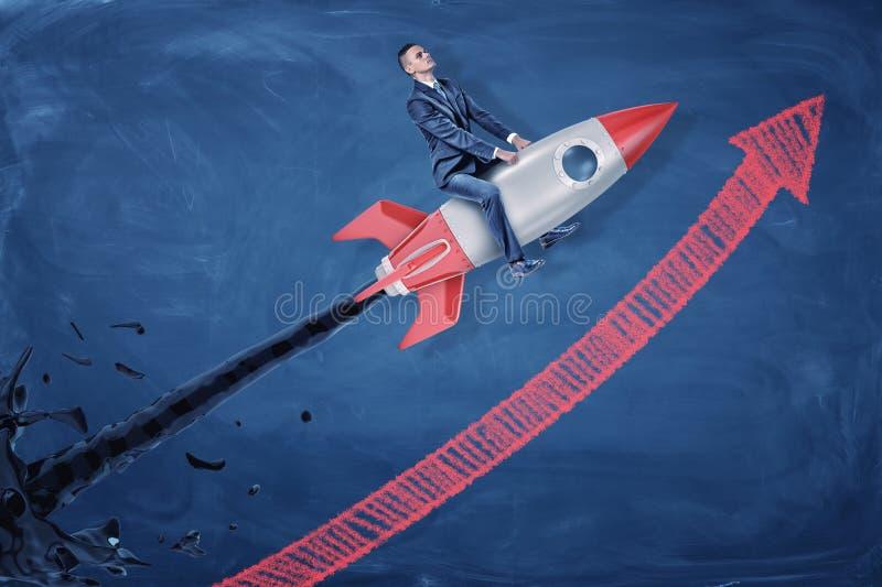 En affärsman rider en silverraket som spurtar svart olja och flyger uppåt längs en stigande pil royaltyfri fotografi