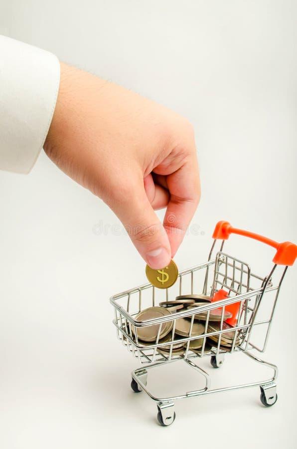 En affärsman sätter ett dollarmynt i en supermarketspårvagn med pengar ackumulation av huvudstad, förhöjning i vinster sparande i royaltyfri foto