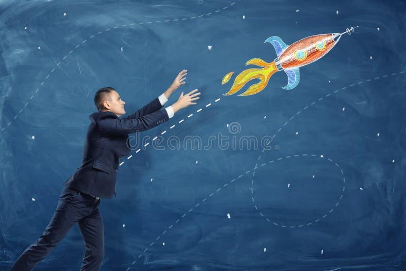 En affärsman som drar upp hans händer till ett flyg till och med himmelraket, målade på en svart tavla royaltyfri foto