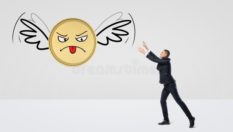 En affärsman som försöker att fånga ett guld- mynt som flyger bort på dess vingar royaltyfri bild