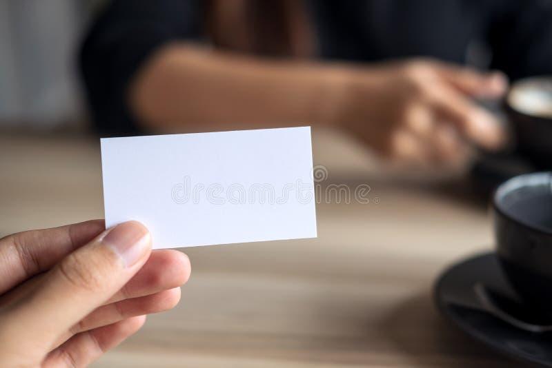 En affärsman som rymmer ett tomt affärskort med affärskvinnan arkivfoton