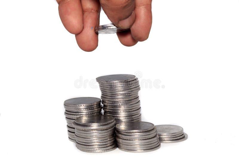 En affärsman som sätter mynt över en bunt av mynt Finansiell, ekonomi-, investering- och besparingbegrepp Packa ihop och utbyteso arkivfoton