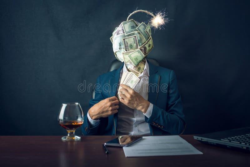 En affärsman som sätter pengar i hans fack med en bombardera i form av räkningar för en bolldollar i stället för hans huvud royaltyfri bild