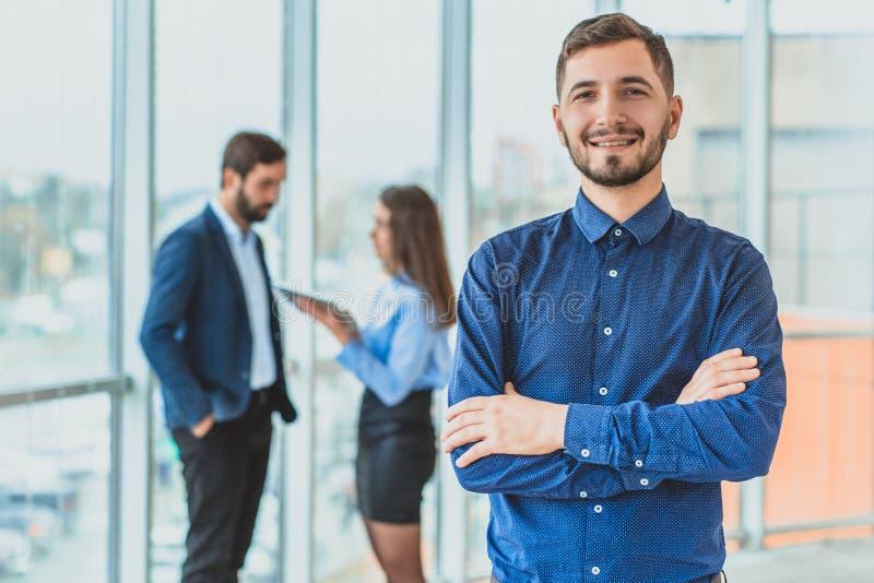 En affärsman står i kontoret vek hans hand till hans hand Under denna tid står han mot bakgrunden royaltyfria foton