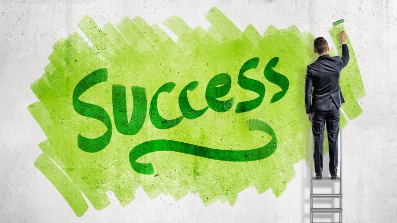 En affärsman står på en trappstege och målar en ordframgång på en grön bakgrund med en målarfärgrulle arkivbilder