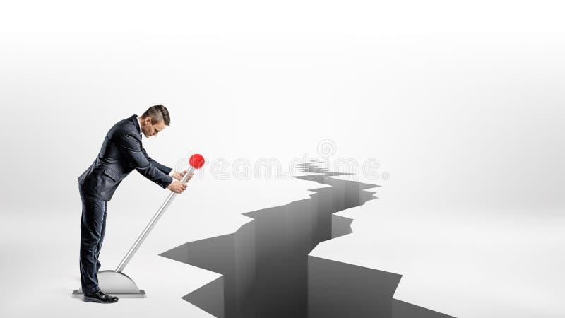 En affärsman vänder en stor metallspak, medan stå bredvid en lång jordskalvklyfta på vit bakgrund arkivfoto