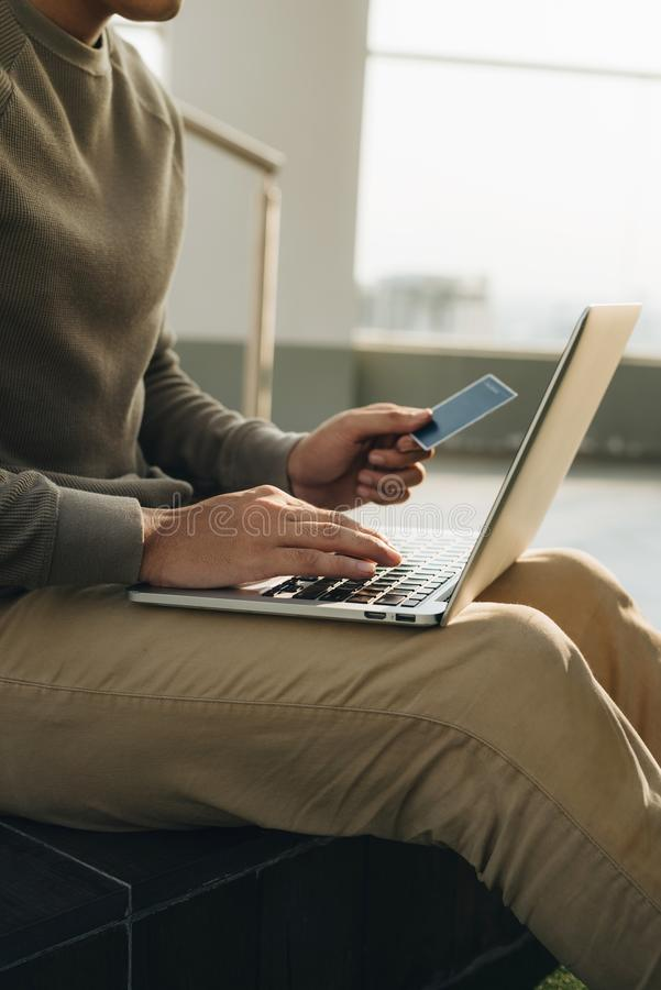 En aff?rsman som sitter med b?rbara datorn p? hans kn? och hand, tar kortet fotografering för bildbyråer
