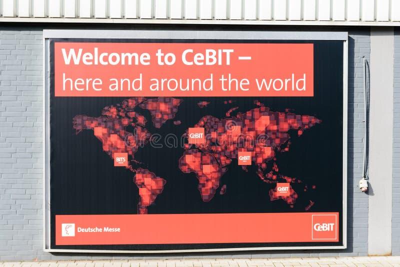 En affisch av CeBITen på en vägg inom jordningen för handelmässan annonserar för CeBIT händelser över hela världen royaltyfria bilder
