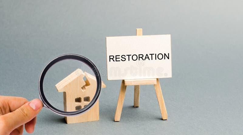 En affisch med inskriftåterställandet och ett brutet trähus Sekundärt hus för reparation Processen av förbättring, royaltyfria bilder