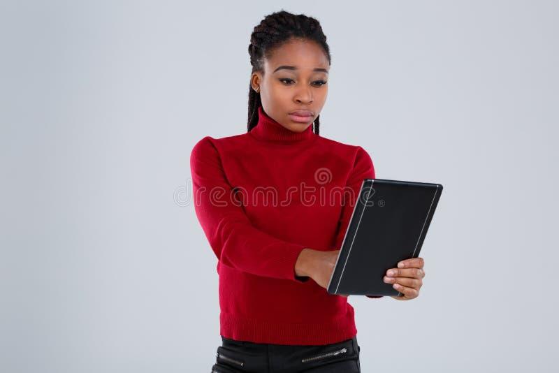 En afrikansk amerikanflicka som fast rymmer en minnestavla och använder den med en allvarlig blick på en grå färgbakgrund royaltyfri bild