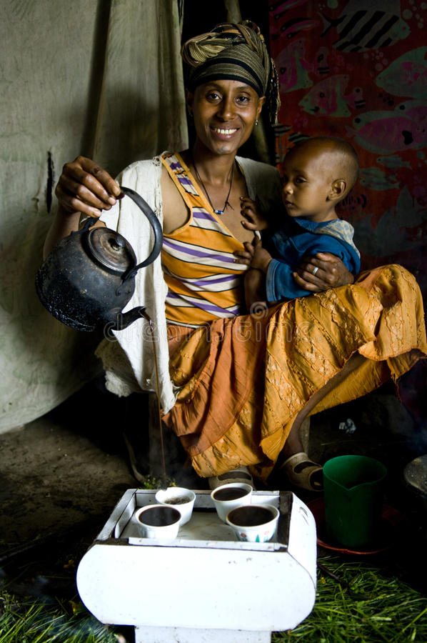 En afrikansk kvinna som utför en kaffeceremoni royaltyfria bilder