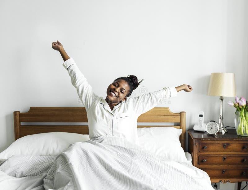 En afrikansk kvinna som vaknar upp i säng royaltyfri fotografi