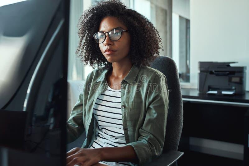 En afrikansk ung affärskvinna som arbetar på hennes skrivbord royaltyfri bild