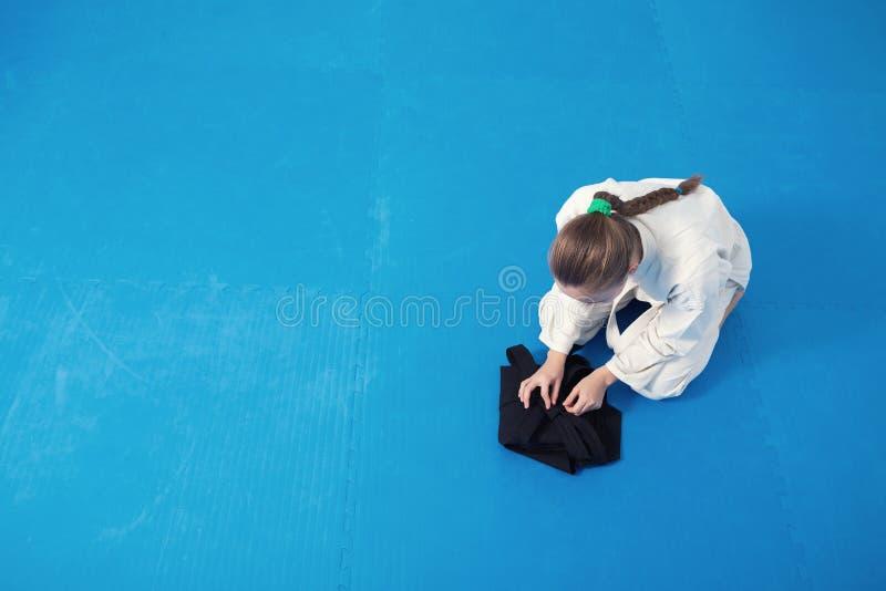En aikidokaflicka som viker hennes hakama arkivfoto